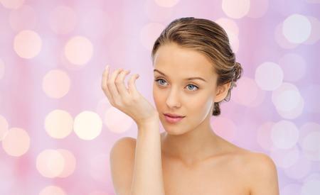 la belleza, el aroma, la gente y el concepto del cuidado del cuerpo - mujer joven con olor a perfume de la muñeca de la mano sobre fondo de color rosa las luces Foto de archivo