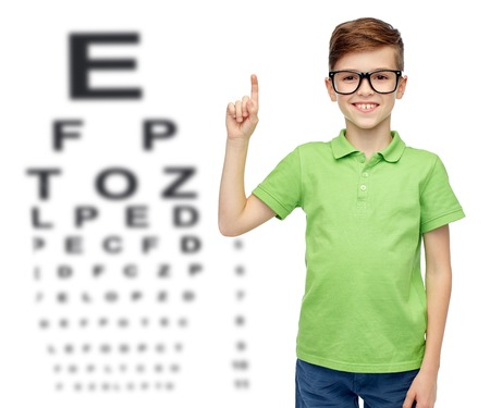 pre teen boys: childhood, vision, eyesight and people concept - happy smiling boy in green polo t-shirt in eyeglasses pointing finger up over eye chart background