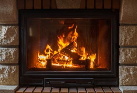 verwarming, warmte, vuur en gezelligheid concept - close-up van brandende open haard thuis Stockfoto