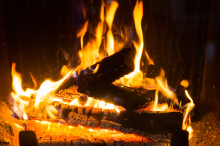 cosiness: heating, warmth, fire and cosiness concept - close up of firewood burning in fireplace Stock Photo