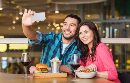 young happy couple: leisure, technology, date, people and holidays concept - happy couple having dinner and taking selfie by smartphone at restaurant