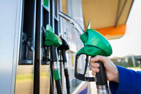 objeto, combustible, aceite, depósito y transporte concepto - cerca de la mano que sostiene la manguera de la gasolina en la gasolinera