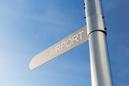 signpost: transportation, direction, location, travel and road sign concept - close up of airport signpost over blue sky background