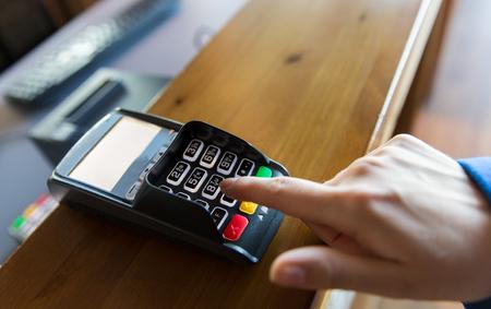 financiën, technologie, betaling en mensen concept - close-up van de hand invoeren van de pincode om geld terminal