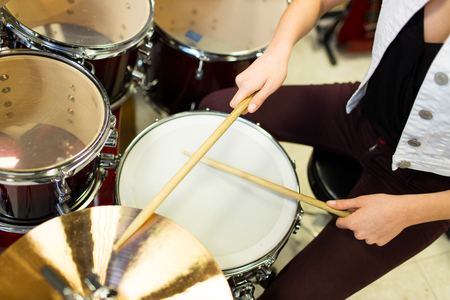 drum kit: music, sale, people, musical instruments and entertainment concept - close up of female musician playing cymbals on drum kit