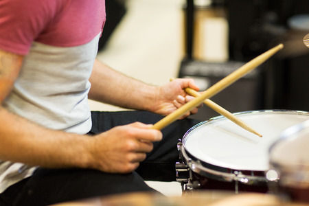 drum kit: music, people, musical instruments and entertainment concept - male musician playing cymbals and pointing drumstick to you at music store Stock Photo
