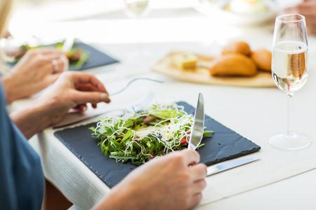 Menschen, Urlaub, Feiern und Lifestyle-Konzept - in der Nähe von Frau essen Salat Appetizer zum Abendessen im Restaurant nach oben
