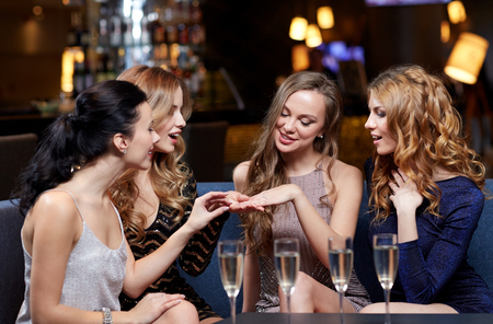 celebration, friends, bachelorette party and holidays concept - happy woman showing engagement ring to her friends with champagne glasses at night club Фото со стока