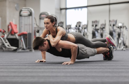 musculine: fitness, sport, training, teamwork and lifestyle concept - smiling couple doing push-ups in the gym