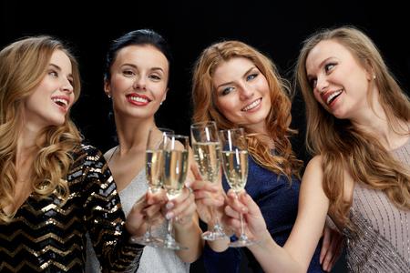 célébration, amis, partie de bachelorette et jours fériés concept - femmes heureuses tintement des verres de champagne sur fond noir