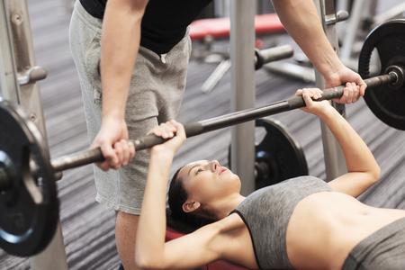 sport, forme physique, le travail d'équipe, l'haltérophilie et les gens notion - jeune femme et un entraîneur personnel avec haltères flexion muscles dans le gymnase
