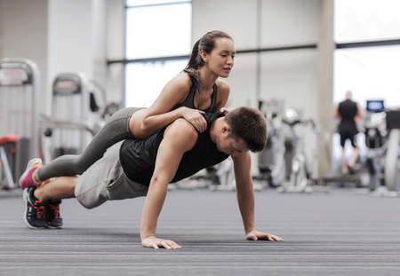 people together: fitness, sport, training, teamwork and lifestyle concept - smiling couple doing push-ups in the gym