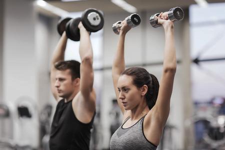 deporte, fitness, estilo de vida y concepto de la gente - hombre sonriente y la mujer con pesas flexionar los músculos en el gimnasio Foto de archivo