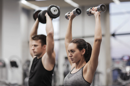 fitness equipment: sport, fitness, lifestyle and people concept - smiling man and woman with dumbbells flexing muscles in gym