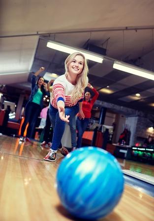 Menschen, Freizeit, Sport und Unterhaltungskonzept - glückliche junge Frau werfen Ball im Bowlingspielklumpen Standard-Bild
