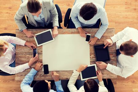 business, people, technology and team work concept - close up of creative team with, blank paper smartphones and tablet pc computers sitting at table in office