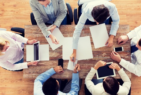 business, people and team work concept - close up of creative team with papers and gadgets meeting in office