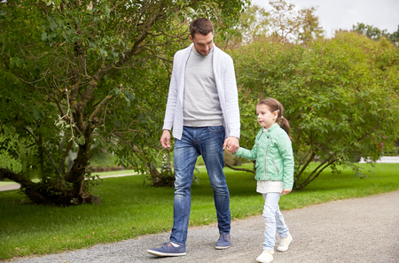 dad and daughter: family, parenthood, fatherhood, adoption and people concept - happy father and little girl walking in summer park