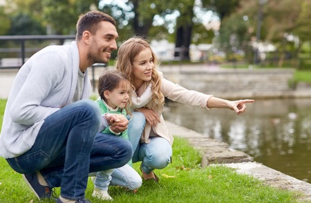 family outdoor: family, parenthood, leisure and people concept - happy mother, father and little girl walking in summer park near pond