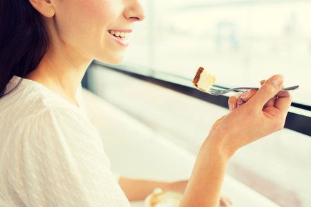 woman eating: food, dessert, people and lifestyle concept - close up of smiling young woman holding fork and eating cake at cafe or home Stock Photo