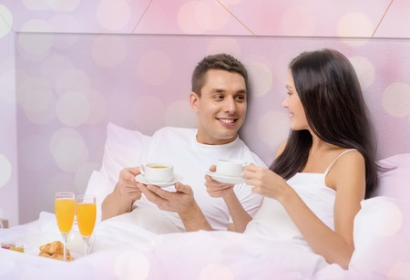 romance bed: vacation, holidays, people, romance and valentines day concept - happy couple having breakfast in bed at hotel or home over lights background Stock Photo