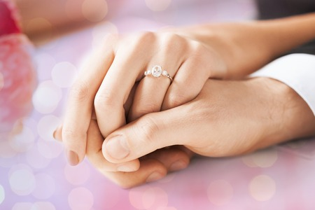 diamond rings: people, holidays, engagement and love concept - close up of engaged couple holding hands with diamond ring over holidays lights background