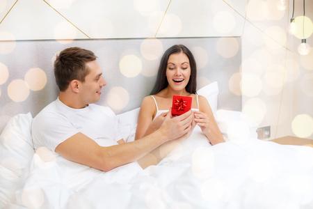 diciembre: amor, días de fiesta, día de San Valentín y concepto de la gente - que mujer hombre feliz pequeña caja de regalo de color rojo en la cama sobre fondo de las luces Foto de archivo