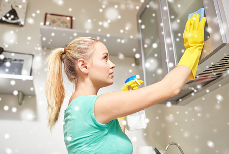 cleanser: people, housework and housekeeping concept - happy woman cleaning cabinet with rag and cleanser at home kitchen over snow effect