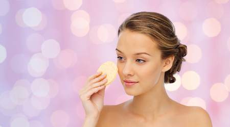 removing make up: beauty, people and skincare concept - young woman cleaning face with exfoliating sponge over pink holidays lights background