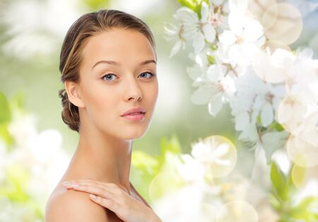 beauty, people, body care and health concept - smiling young woman face and hand on bare shoulder over green natural cherry blossom background