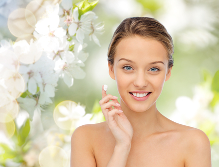 beauty, people, cosmetics, skincare and health concept - happy smiling young woman applying cream to her face over green natural cherry blossom background