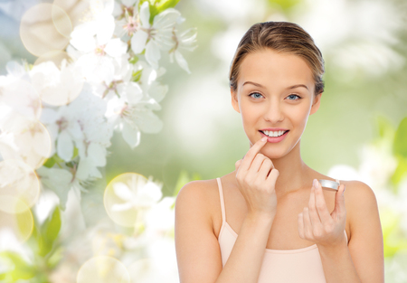 gloss: beauty, people and lip care concept - smiling young woman applying lip balm to her lips over green natural cherry blossom background