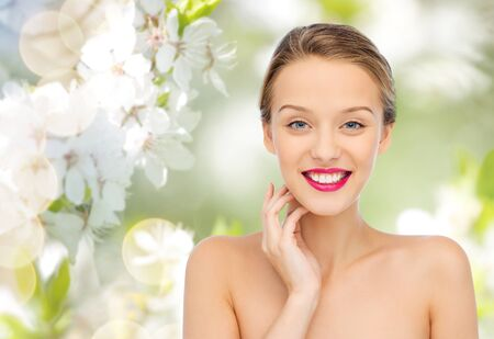 beauty, people and health concept - smiling young woman face with pink lipstick on lips and shoulders over green natural cherry blossom background Stock Photo
