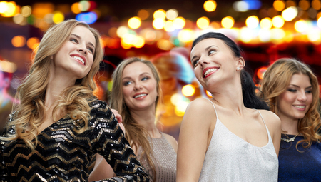 party night: party, holidays, nightlife and people concept - happy young women dancing over night club disco lights background