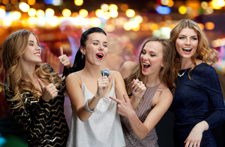 nice girl: holidays, friends, bachelorette party, nightlife and people concept - three women in evening dresses with microphone singing karaoke over night club disco lights background