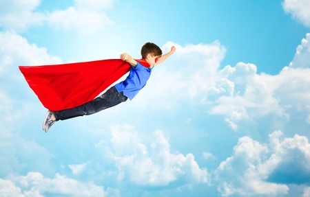 pre teen boys: happiness, freedom, childhood, movement and people concept - boy in red superhero cape and mask flying in air over blue sky and clouds background