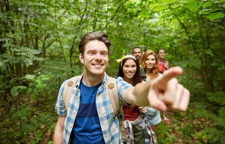in the woods: adventure, travel, tourism, hike and people concept - group of smiling friends with backpacks pointing finger in woods