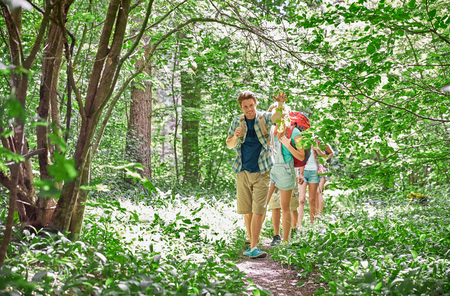 hiking: adventure, travel, tourism, hike and people concept - group of smiling friends walking with backpacks in woods