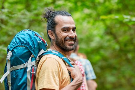 in the woods: adventure, travel, tourism, hike and people concept - group of smiling friends walking with backpacks in woods