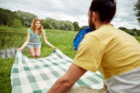 campsite: camping, travel, tourism, hike and people concept - happy couple laying picnic blanket at campsite