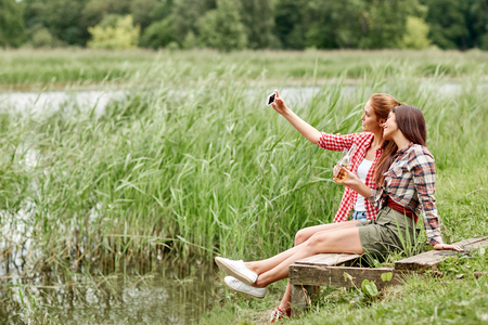young women: camping, travel, tourism, hike and people concept - happy young women with glass bottles drinking cider or beer and taking selfie by smartphone outdoors