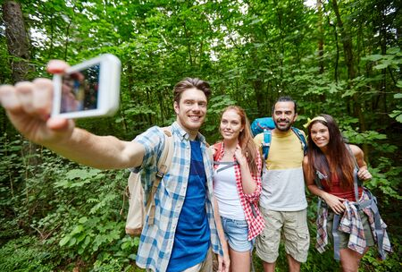 in the woods: technology, travel, tourism, hike and people concept - group of smiling friends walking with backpacks taking selfie by smartphone in woods Stock Photo