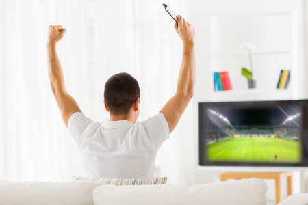 people watching: leisure, technology, media, sport and people concept - man watching football game on tv and supporting team at home from back