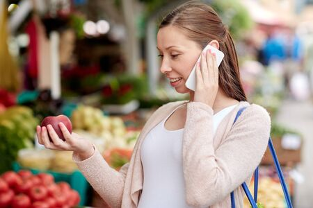street market: sale, shopping, food, pregnancy and people concept - happy pregnant woman choosing fruits and calling on smartphone at street market Stock Photo