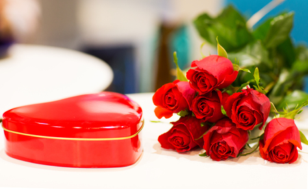 attentions: love, date, romance, valentines day and holidays concept - close up of red heart shaped chocolate box and rose flowers on table Stock Photo