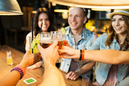 pub: leisure, celebraton, friendship, people and holidays concept - happy friends clinking glasses at bar or pub
