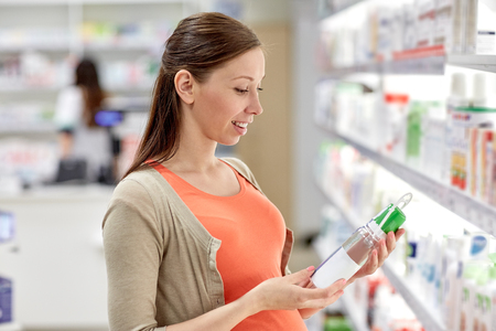 pharmaceutic: pregnancy, medicine, pharmaceutics, health care and people concept - happy pregnant woman choosing anti stretch marks lotion at pharmacy