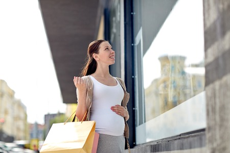pregnancy, motherhood, people and expectation concept - happy smiling pregnant woman with shopping bags at city street Stock Photo