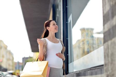 Schwangerschaft, Mutterschaft, Menschen und Erwartung Konzept - glücklich lächelnd schwangere Frau mit Einkaufstüten auf Stadtstraße