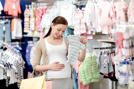 expectation: pregnancy, people, sale and expectation concept - happy pregnant woman with shopping bag buying baby bodysuit at children clothing store
